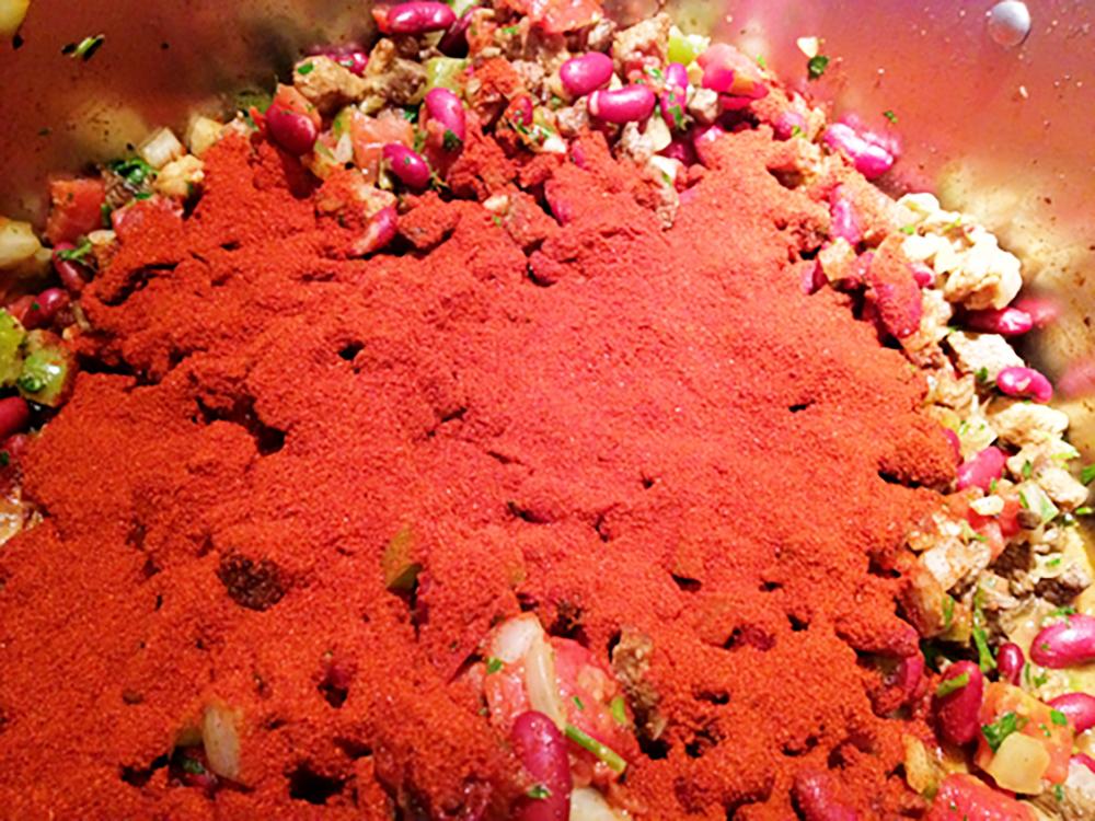 Add chili powder, salt, pepper and cumin and mix.