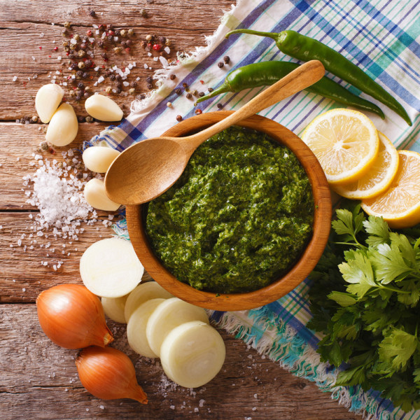 Green spicy sauce chimichurri and ingredients close-up. Horizontal top view